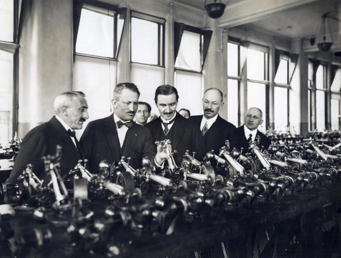 Een afvaardiging Poolse diplomaten kijkt geïnteresseerd naar de kleine apparaten waarmee diamanten worden gezaagd.