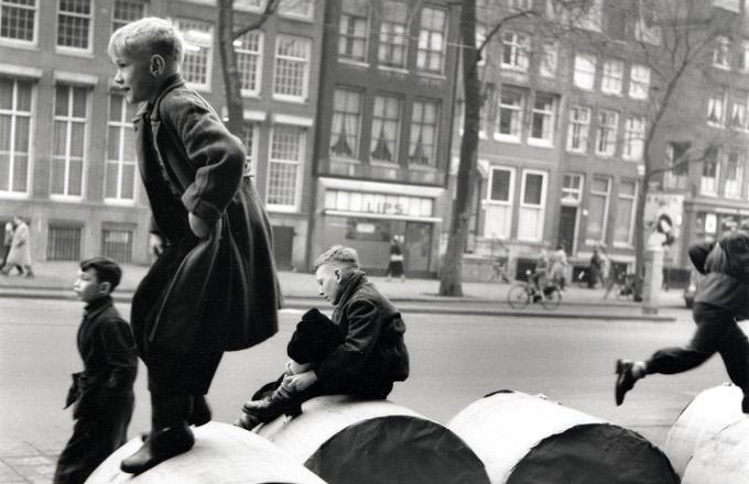 Amsterdamse jongens spelen buiten op papierrollen die voor de krant bestemd zijn