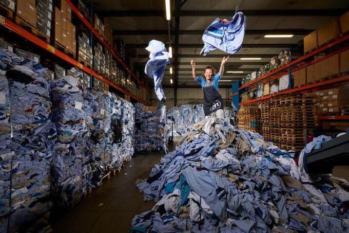 Geloof het of niet, maar deze bergen afgedankte kleding worden straks weer nieuwe bedrijfskleding voor Albert Heijn