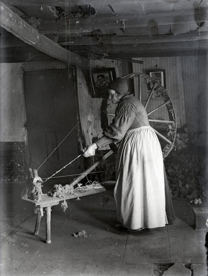 Op een middeleeuws spinnewiel draait deze thuisspinster haar draden van wol. Daar is wel wat handigheid voor nodig