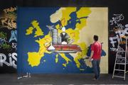 "A man working on a graffiti illustrating the fourth priority of the Juncker Commission: ""Internal Market"""