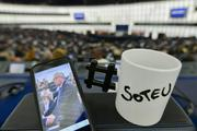 "A smartphone showing a photograph of Jean-Claude Juncker, next to white mug with the black inscription ""SOTEU"" (State of the Union) on it, and with a # (hashtag) handle"
