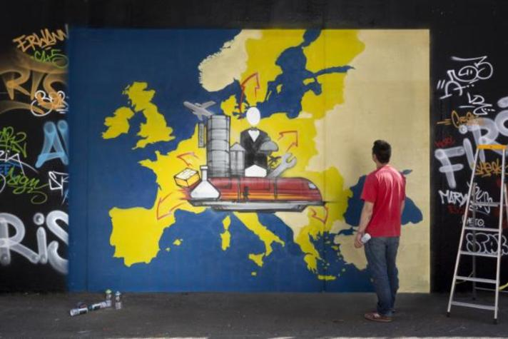 """A man working on a graffiti illustrating the fourth priority of the Juncker Commission: """"Internal Market"""""""