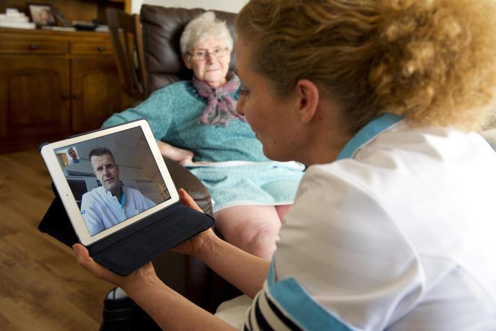 Wijkverpleegkundige heeft via de iPad contact met de dokter over een aandoening bij een patiënt