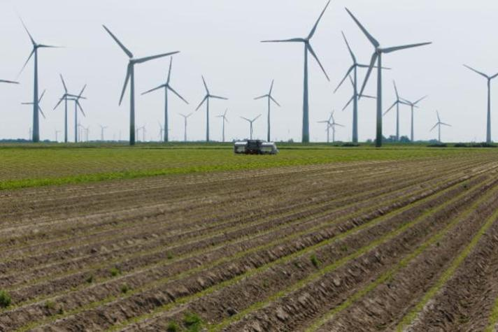 A solar powered weeding machine in the fields, with wind turbines in the background
